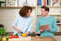 Husband and wife reading recipe from tablet Stock Photos