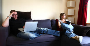 Husband and Wife Relaxing on the Sofa Stock Images