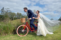 Husband and wife ride on bicycle on their wedding Day Royalty Free Stock Image