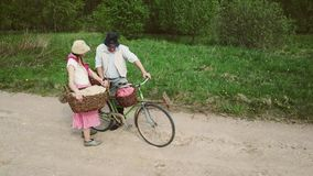 Husband and wife are on the road with a bicycle. stock footage