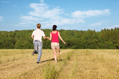 Husband and wife running in field Stock Photography