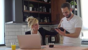 Husband and wife searching internet during coffee break and getting a great news in their kitchen.  stock video footage