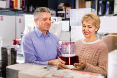 Husband and wife in shop of household appliances choose juicer. Happy cheerful husband and wife in shop of household appliances choose juicer and chopper for royalty free stock image