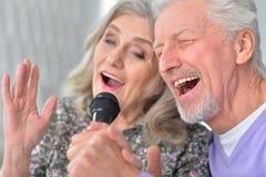 Husband and wife singing songs. Senior couple husband and wife singing songs stock photos