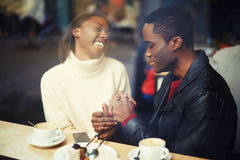 Husband and wife sit with a cafe holding hands Royalty Free Stock Images