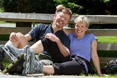 Husband and wife sitting and leaning against a fence wearing inline skates. Stock Photography