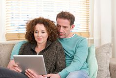 Husband and wife sitting on sofa at home looking at tablet Royalty Free Stock Photo