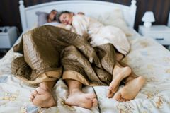 Husband and wife sleeping in bed together partially covered. With naked legs stock images