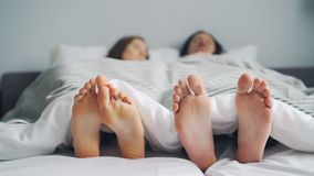 Husband and wife sleeping in bed under blanket together, focus on feet. Husband and wife are sleeping in bed under clean white blanket together, focus on bare stock video footage