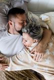 Husband and wife sleeping together in one bed - in hug. Husband and wife sleeping together in hug in one bed, top view royalty free stock photography