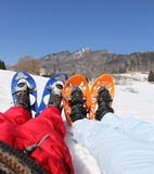Husband and wife with snowshoes in the mountains. Husband and wife with blue and orange snowshoes in the mountains Stock Photography