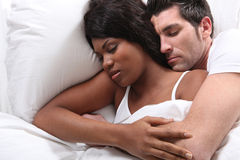 Husband and wife snuggling in bed Stock Photo
