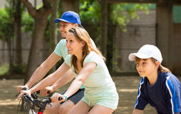 Husband with wife and son riding bicycles in park Royalty Free Stock Photography