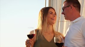 Husband and wife are spending their vacation sailing on the yacht and drinking wine. Beautiful young couple is sailing river together during romantic weekend stock video footage