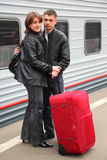 Husband and wife stand on perron near train stock photography