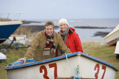 Husband and wife standing in boat on beach Royalty Free Stock Image