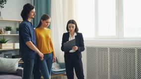 Husband and wife talking to housing agent looking at documents and apartment. Husband and wife are talking to housing agent cheerful young lady looking at stock video footage