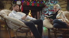 Husband and wife talks while reading book and surfing the Internet on smartphone in Christmas night. Husband and wife talks while reading book and surfing the stock video footage