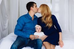 The husband and wife tenderly kiss each other and between them sits their little daughter. Family harmony of attitude. The husband and wife tenderly kiss each royalty free stock photo