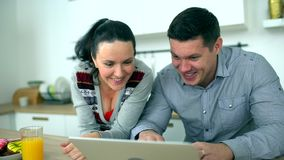 Caucasian couple is using computer at kitchen. Home, technology and relationships concept - smiling husband and wife
