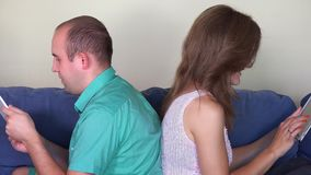 Husband and wife using own tablet computers sitting on sofa back to back stock footage
