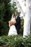 Husband and wife - wedding series. Wedding bride and her new husband. She is holding her beautiful bridal bouquet of flowers. They are looking at the camera royalty free stock photos