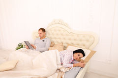 Husband works on tablet while wife sleeping in white bed Royalty Free Stock Photos