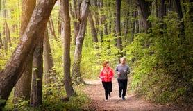 Husbanf和妻子佩带的运动服和赛跑在森林里 免版税图库摄影