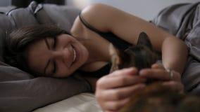 Husdjur komfort, vilar och folkbegreppet - lycklig ung kvinna med katten som hemma ligger i säng Brunettflickan kopplade av smekn lager videofilmer