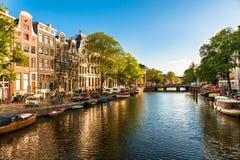 Häuser und Boote auf Amsterdam-Kanal Stockbilder