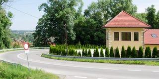 Huset med det röda taket står nära vägen Arkivbild
