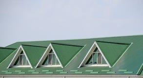 Huset med plast- fönster och ett grönt tak av det korrugerade arket Grönt tak av den korrugerade metallprofilen och plast-fönster Royaltyfria Foton