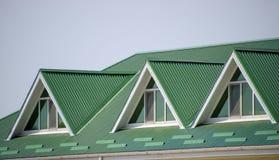 Huset med plast- fönster och ett grönt tak av det korrugerade arket Grönt tak av den korrugerade metallprofilen och plast-fönster Arkivbild