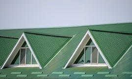 Huset med plast- fönster och ett grönt tak av det korrugerade arket Grönt tak av den korrugerade metallprofilen och plast-fönster Arkivbilder