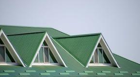 Huset med plast- fönster och ett grönt tak av det korrugerade arket Grönt tak av den korrugerade metallprofilen och plast-fönster Arkivfoto