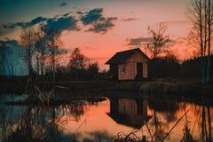 Huset på sjön reflekterade på vatten i skymning arkivfoton