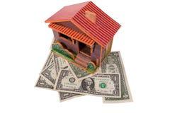 Huset står på dollar som isoleras på vit bakgrund Royaltyfri Fotografi