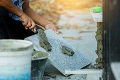 Husförbättring, renovering, arbetare för konstruktionsbransch som installerar granitstentegelplattor med cement royaltyfria bilder