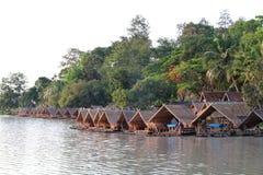 Husfartyg på sjön med träd som tillbaka malde Arkivbild