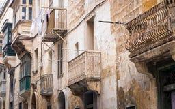Husfasad med den färgrika, forntida och roliga balkongen på republikgatan i Valletta, Malta arkivfoto