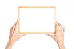 Husgarnering och fotoramämne: mänsklig hand som rymmer en träbildram isolerad på en vit bakgrund i studiogranen Royaltyfri Fotografi
