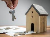 Hushållbesparingar och finanser, hand som rymmer tangenten med modellhuset r arkivbild