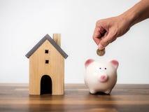 Hushållbesparingar och finanser, hand som sätter myntet i spargrisen coins sparande för stapel för begreppshandpengar skyddande arkivfoton