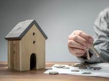 Hushållbesparingar och finanser, man som rymmer tangenten med modellhuset coins sparande för stapel för begreppshandpengar skydda arkivbild