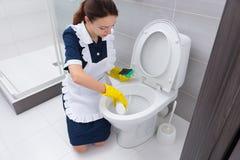 Hushållerska som skurar ner toalett i badrum Arkivbilder