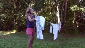 Hushållerskakvinnan tar av torkad kläder från utomhus- rep mellan träd 4K stock video