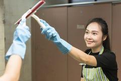 Hushållning eller hembiträde som gör ren en smutsig spegel royaltyfri bild