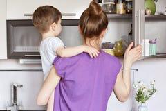 Hushållsarbete, barn och moderskapbegrepp Upptagna hemmafruförsök att finna nödvändiga produkter i hylla av kök, håll litet K Arkivfoton