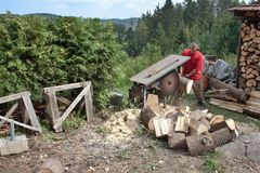 Hushållsarbete man klipper trä, förberedelsen för vinter Arkivfoto