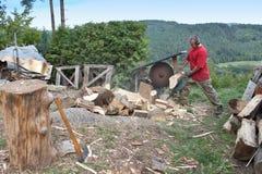 Hushållsarbete man klipper trä, förberedelsen för vinter Arkivfoton